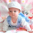 Beautiful baby girl in funny cap lying and looking with interest — Stock Photo