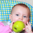 Closeup portrait of beautiful baby girl eating big green apple s — Stock Photo