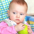 Closeup colorful portrait of beautiful baby girl holding green apple — Stock Photo