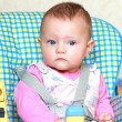 Beautiful thinking baby girl sitting on the bright blue chair — ストック写真