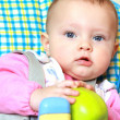 Closeup portrait of baby girl holding green apple sitting on cha — Stock Photo #9163401