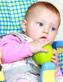 Closeup portrait of surprised baby girl holding green apple and — Stock Photo