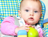 Closeup portrait of baby girl holding green apple sitting on cha — Stock Photo