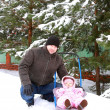 图库照片: Handsome father sitting with baby girl on snow sleigh on winter