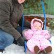 Handsome father walking with baby girl on snow sleigh on winter — Stock Photo