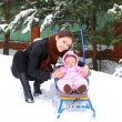 Foto Stock: Beautiful young mother with small baby girl walking on winter we