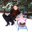 Beautiful young mother with small baby girl walking on winter we — Stock Photo