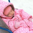 Stock Photo: Beautiful baby girl in pink warm dress sleeping on sleigh on win