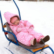 Beautiful baby girl in pink warm dress sleeping on sleigh on win — Stock Photo