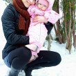 beautiful young mother holding little baby girl on winter backgr — Stock Photo