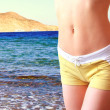 Fit female body in shorts on beautiful blue sea background — Stock Photo