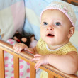 Beautiful funny baby girl with blue eyes looking up standing in — Stock Photo