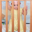 Beautiful baby girl in dress peeping out of wooden safety bed — Stock Photo