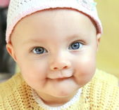 Closeup portrait of funny baby girl with blue big eyes in hat — Stock Photo