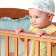 Beautiful smiling baby girl in hat standing in wooden bed isolat — Stock Photo