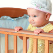Stock Photo: Beautiful smiling baby girl in hat standing in wooden bed isolat