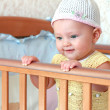 Beautiful happy baby girl in funny white hat standing in bed — Stock Photo