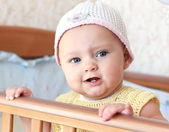 Beautiful angry baby girl in funny hat standing in bed and looki — Stock Photo