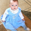 Pretty baby girl sitting in blue dress and looking in camera — Stock Photo
