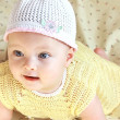 Closeup portrait of happy baby girl in white hat with flower — ストック写真