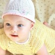 Closeup portrait of happy baby girl in white hat with flower — Stock Photo