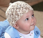 Closeup portrait of baby girl in white hat looking with interest — Stockfoto