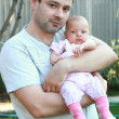 Portrait of handsome father holding little baby girl on the hand — Stock Photo