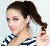 Beautiful young woman holding the hair with flirting look — Stock Photo