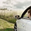 Stock Photo: Beautiful woman looking from window of car on nature dark blue s