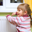 Girl warm one's hands near radiator. - Stock Photo