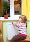 Girl warm one's hands near radiator. — Stock Photo