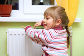 Girl warm one's hands near radiator. — Stockfoto