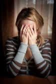 Ayoung woman took her hands face — Stock Photo