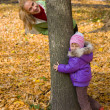 Woman flees with her daughter in the autumn park — Stock Photo #9618391