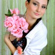 The young beautiful girl the brunette with pink roses in hands — Stock Photo