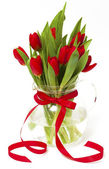 Red tulips in a vase with a red ribbon — Stock Photo