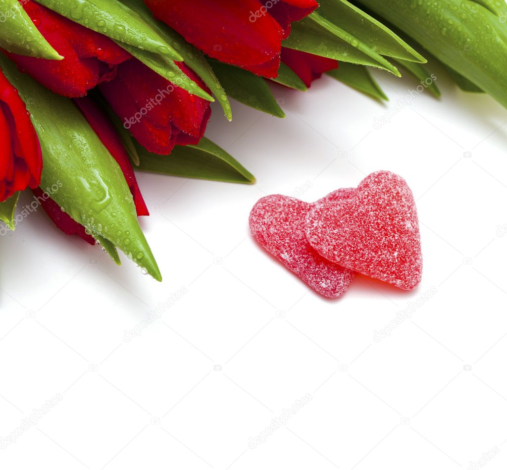 Red tulips and two heart-shaped candies and copy space for your text — Stock Photo #8928458