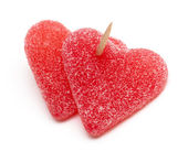 Two heart-shaped candies atached to each other with a toothpick — Stock Photo