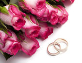Pink roses with droplets and wedding rings — Stock Photo
