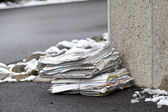Stack of newspaper on a winter street — Stock Photo