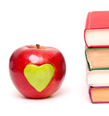 Apple with green heart and stack of books — Stock Photo