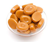 Caramel candies in a glass bowl — Stock Photo
