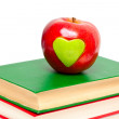 Apple with green heart on stack of books — Stock Photo #9781494