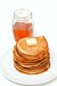 Golden buttermilk pancakes and jar of honey — Stock Photo
