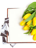 Yellow tulips lying on book with black and white photographs — Stock Photo