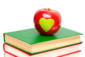Apple with green heart on stack of books — Stock Photo