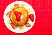 Golden buttermilch pfannkuchen mit erdbeeren und banane auf rot — Stockfoto