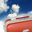 Orange suitcase with sky backdrop - Stock Photo