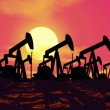 Oil well silhouetted against deep red evening sunset — Stock Photo