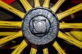 Fragment of old wagon wheel with yellow spikes — Stock Photo